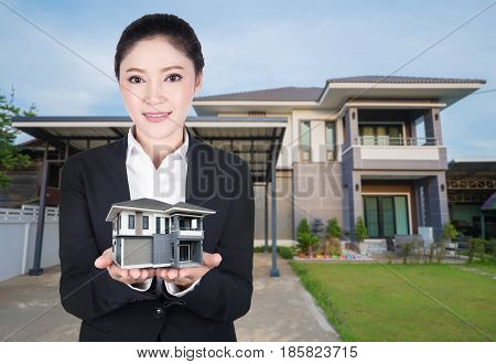 Model House In Business Woman Hand With Actual House And Garden