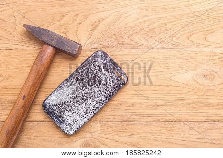 Broken Of Black Smartphone And Hammer On Wooden Table Background