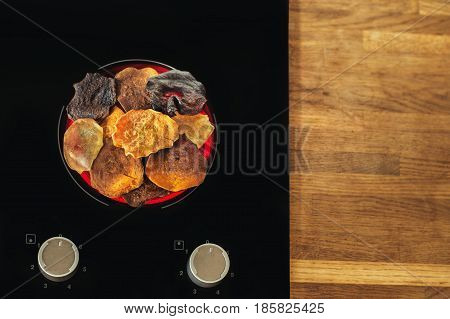 Vegetable chips lie on an electric stove and cook. Preparation of vegetable and potato chips