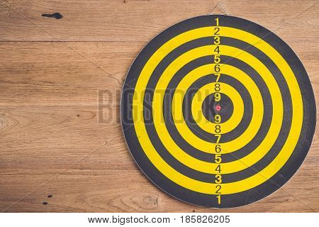 Dart Arrow And Dartboard On Brown Wooden Background. Composition White Free Space For Text Or Design