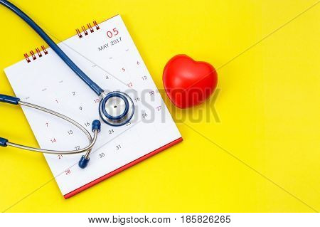 Blue Stethoscope On White Calendar And Red Heart Shape On Yellow Background. Schedule To Check Heart