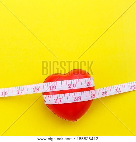 Red Heart Shape And White Measurement Tape On Yellow Background. For Heart Check Up Or Checking Size