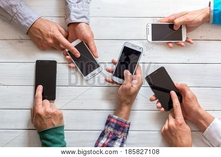 Mobile phones in friends hand closeup. Network addicted concept