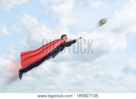 A businessman in a superhero cape flying in the sky trying to catch a 100 USD banknote. Business aspirations. Impossible effort. Fortune and profit.