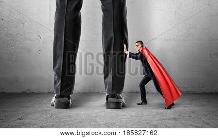 A small businessman in a superman cape trying to push away giant man legs. Uneven competition. Best performance. Business problems.