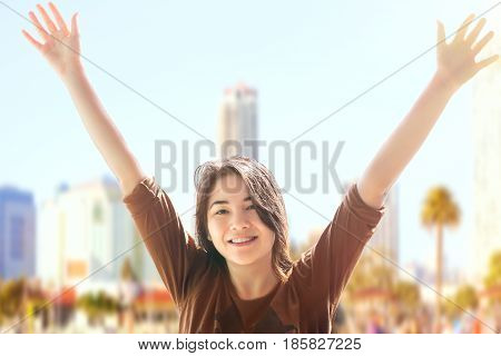 Beautiful biracial teen girl smiling with arms raised on sunny day with urban background scene