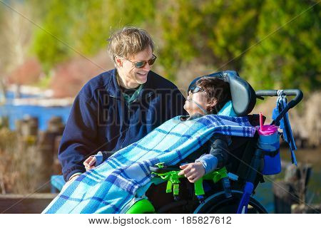 Disabled biracial ten year old boy in wheelchair talking with father at lakeside park on sunny day in chilly weather