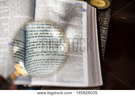 Reading the Holy Bible with a magnify glass