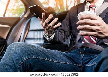 Young Handsome Businessman Working In Back Of Car And Using A Tablet Or Smart Phone
