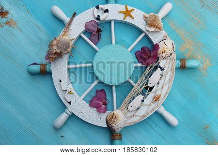 Wooden Boat or Ship Steering Wheel Fishing Net Shell with flower petals on a wooden blue background