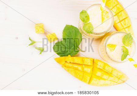 Freshly blended yellow mango fruit smoothie in glass jars with straw mint leaves mango slices top view. White wooden board background copy space.