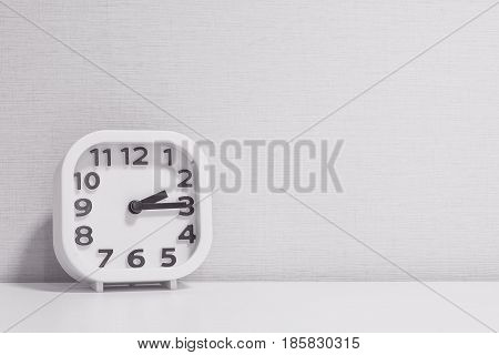 Closeup white clock for decorate show a quarter past two o'clock or 2:15 p.m. on white wood desk and cream wallpaper textured background in black and white tone with copy space