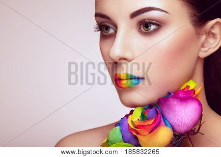 Portrait of beautiful young woman with rainbow rose. Bright colors. Vivid colorful lips. Rainbow make up. Multicolored flowers