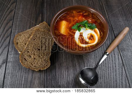 Tomato soup . Traditional  Ukrainian beetroot and tomato soup - borsch in clay pot with sour cream, herbs and bread on dark wooden background.