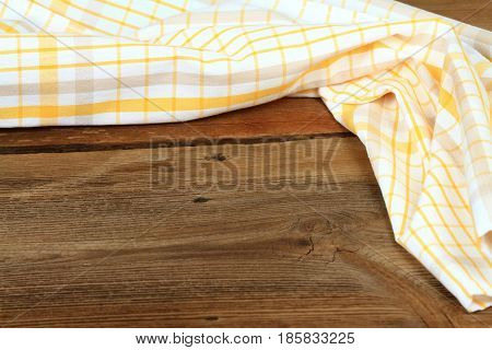 Dish cloth in yellow and white on brown wooden table. Linen tea towel on board good for background