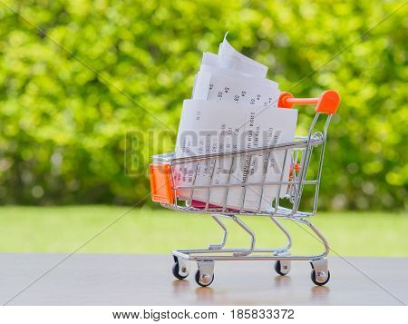 Shopping cart with receiptwith coins on wooden table concept for grocery expenses and consumerism