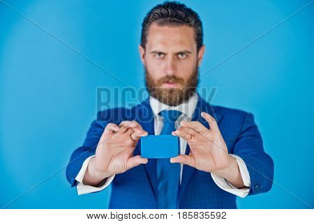 portrait of man holding card in business suit on blue background copy space