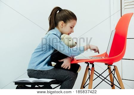 Adorable Girl Typing On Laptop And Hugging Teddy Bear
