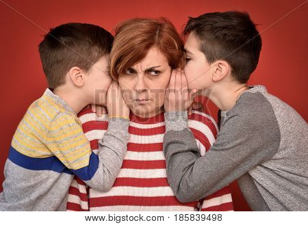 Sons whispering secret into ears of angry mother