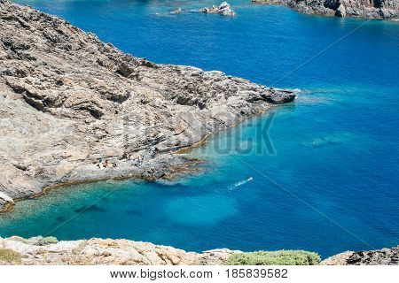 Rocky shore and calm deep blue ocean from above. Horizontal outdoors shot.