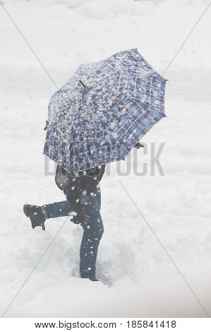 Lonely man with umbrella in the snowstorm