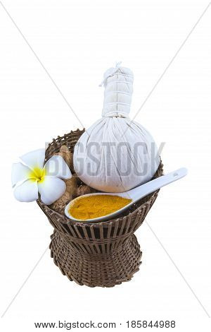 Spa herbal compressing ball white frangipani flowers (Plumeria spp Apocynaceae Pagoda tree Temple tree) turmeric powder in white spoon and candle in bamboo basket isolated on white background.Saved with clipping path.