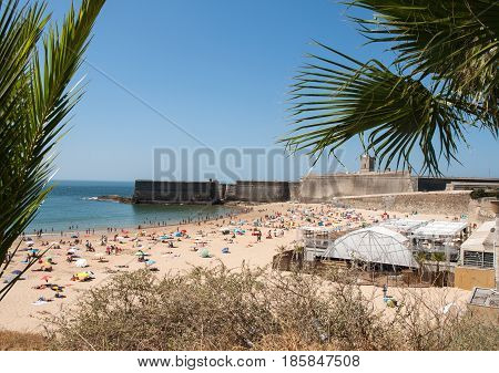 CASCAIS PORTUGAL - AUGUST 1 2015: People sunbathing on the beach in Cascais Portugal. Cascais is famous and popular summer vacation spot for Portuguese and foreign tourists