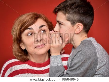 Young boy whispering secret into ears of smiling mother