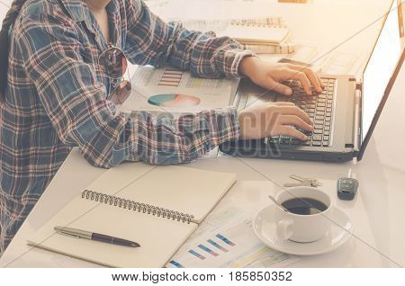 Woman's hand placed on the keyboard of the notebook is placed on a wooden table with a working device and placed in a glass coffee morning.