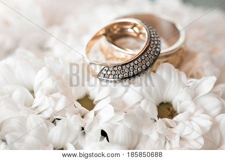 Wedding rings on a white flowers. accessories wedding closeup. selective focus.