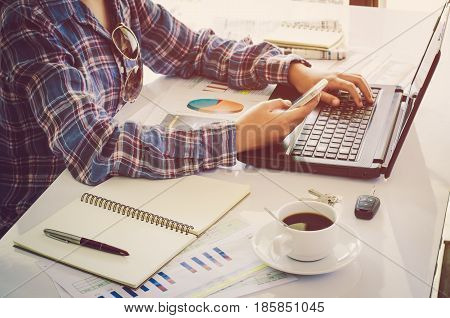 Woman's hand placed on the keyboard of the notebook and holding smart phone is placed on a wooden table with a working device and placed in a glass coffee .