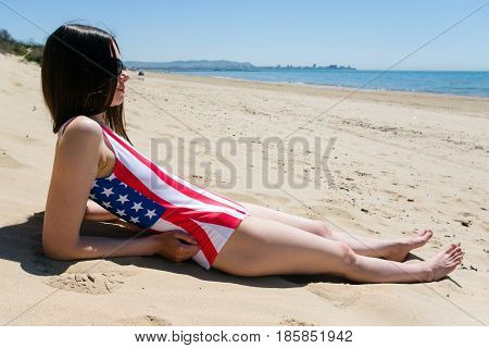A young woman patriot lies on the beach in a bathing suit the colors of the US flag.