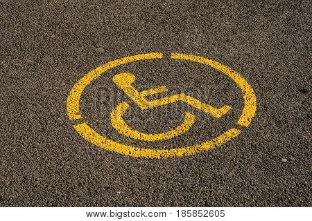 Parking space sign on asphalt surface - reserved lot for person with disability