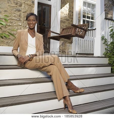 Mixed race woman sitting on front steps
