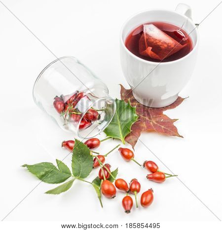 Bunch of rose hips spreaded on white background with rose hip tea and autumn leaves, symbolising that eating and drinking of rose hip products are healthy and are helping to prevent diseases, symbols of autumn nature