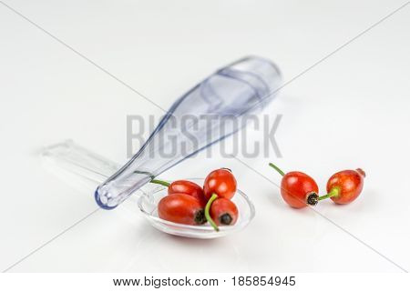 Rose hip on a medicine spoon on white background with the case of temperature indicator, symbolising that drinking and eating of rose hip products prevents diseases like flu, sore throat, high temperature etc.