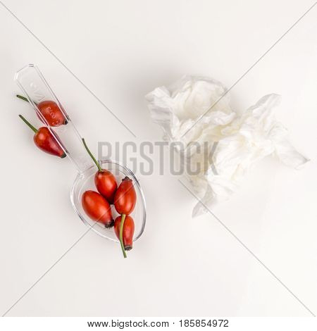Rose hip of a medicine spoon on the table with used handkerchief tissue