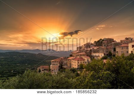 Ancient hilltop village of Belgodere in the Balagne region of Corsica lit up by a dramatic evening sunset