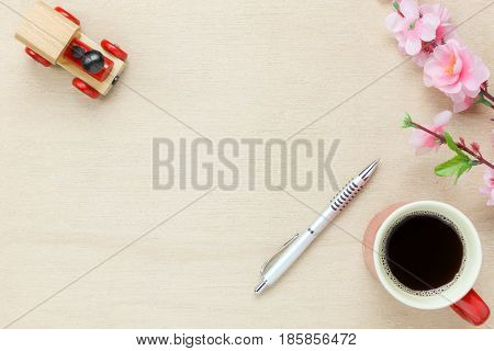 Top view business office desk background.The silver pen coffee beautiful pink flower toy car on wooden table backgtound with copy space.