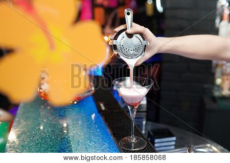Expert barman is making cocktail at night club.