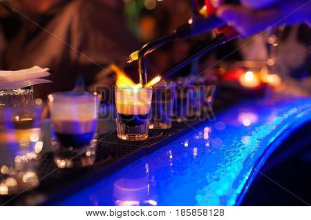The bartender makes hot alcoholic cocktail and ignites bar. elite night club during party prepares a fiery cocktail. Fire on bar