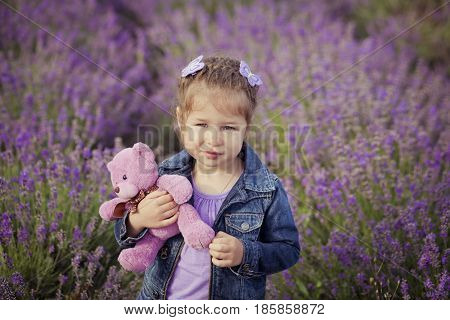 Pretty young girl sitting in lavender field in nice hat boater with purple flower on it