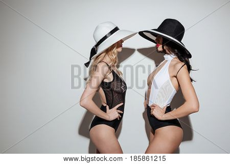 Photo of two young ladies with bright makeup lips wearing hat dressed in swimwear standing isolated. Looking aside.