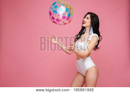 Portrait of a happy brunette woman wearing swimsuit and playing with beach ball isolated over pink background
