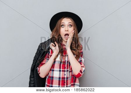 Portrait of a surprised astonished cute girl in plaid shirt holding hand at her face and looking at camera isolated over gray background