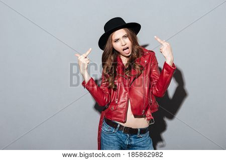 Image of screaming young angry woman standing over grey wall wearing hat showing middle finger. Looking at camera.