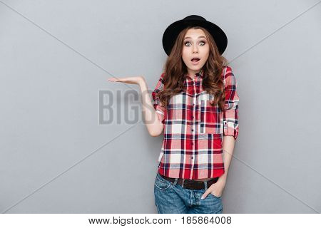 Portrait of a surprised shocked young woman in plaid shirt holding copyspace on her palm and looking at camera isolated over gray background