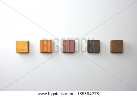 Index, menu or cover abstract back ground, consisting of five colored wooden blocks. On natural white background, with highlight on upper left. Earth color. Light brown to brown.