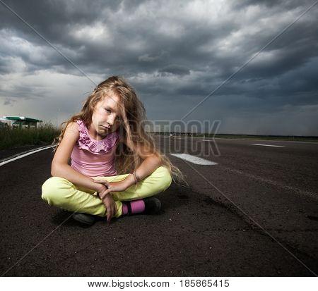 Sad girl near road. Child outdoors