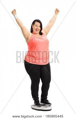 Full length portrait of an overweight woman standing on a weight scale and gesturing happiness isolated on white background